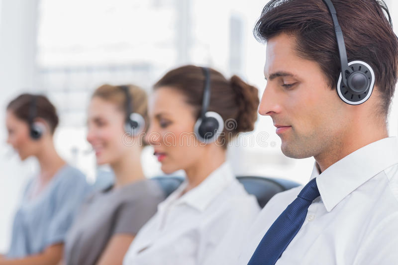 Group of agents sitting in line in a call centre. Group of agents sitting in line in a bright call centre royalty free stock photo