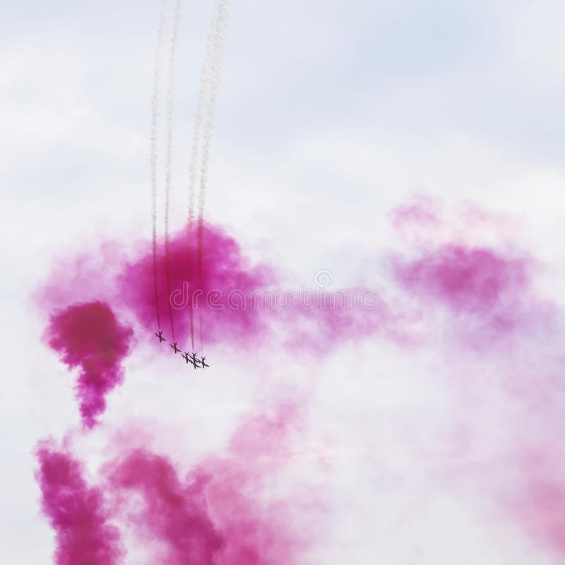 Group of aircraft flying in bright, ring of smoke, sangria color. Airplanes on aerobatic show. Exciting performance. Air stock photo