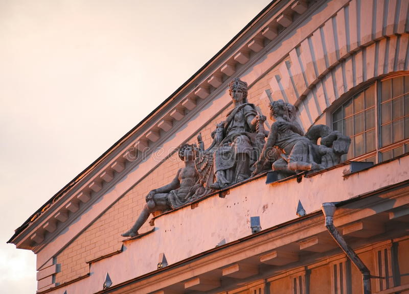 Group of allegorical sculpture in antique style. Decorative sculptural elements on the facade of the old historic building. The low sun, summer 2013. the royalty free stock photo