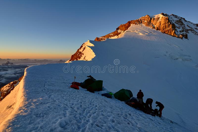 Group alpinists in base camp on snowy peak places tent at sunset, pass Mirali, 5300, Fann, Pamir Alay, Tajikistan stock photos