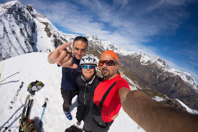 Group of alpinists selfie on mountain top. Scenic high altitude background on snow capped Alps, sunny day. Sestriere, Italy - April 14, 2016: Group of alpinists royalty free stock image