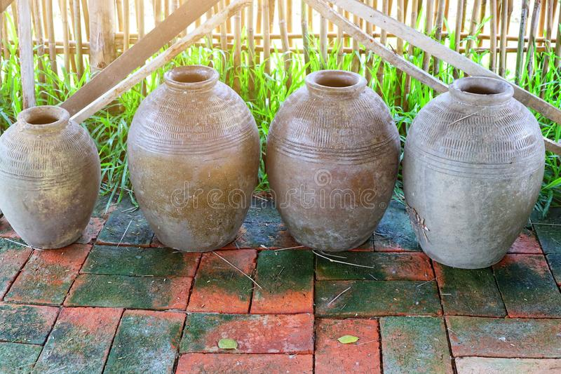 A group of ancient earthenware containers for placing water on brick floors, vintage tone images. Thailand stock images