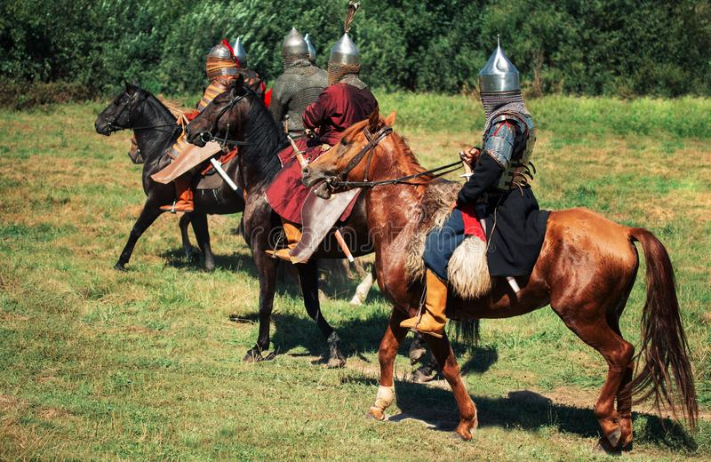Group of ancient equestrians in historical costumes are reconstructed. The medieval armored knights are on the horses. The historical reenactors are in the stock image