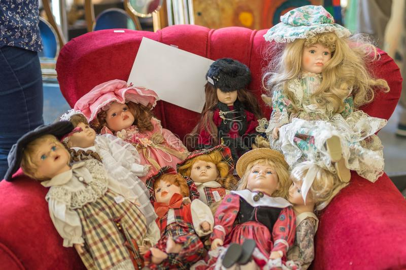 Group of Antique Dolls on a Red Couch stock image