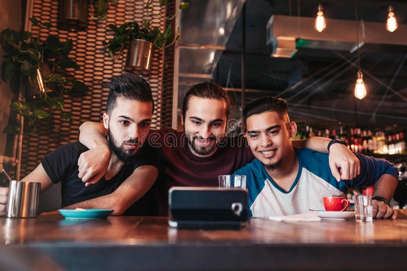 Group of arab friends taking selfie in lounge bar. Mixed race young men having fun royalty free stock photos