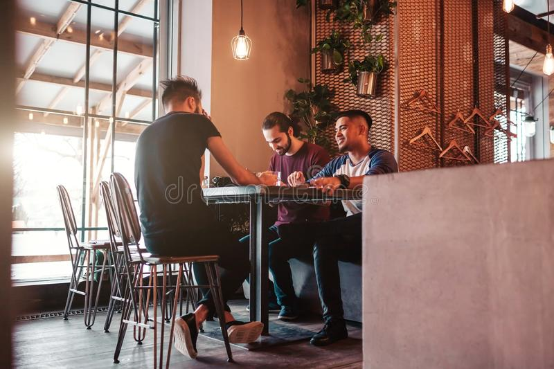 Group of arab friends taking selfie in lounge bar. Mixed race young men having fun. In loft cafe stock image
