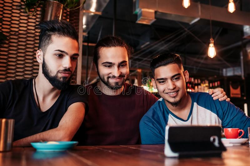 Group of arabian friends taking selfie in lounge bar. Mixed race young men having fun. In loft cafe. Hipsters hangout together stock photo