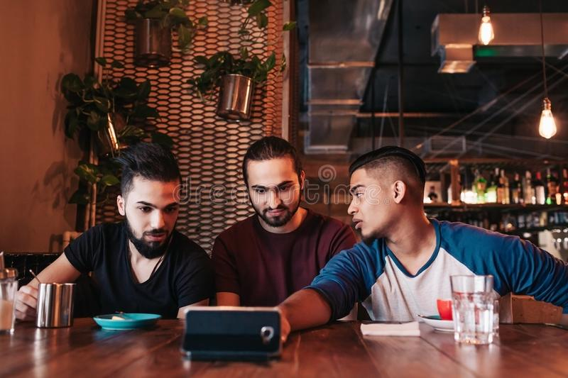 Group of arabian friends taking selfie in lounge bar. Mixed race young men having fun. In loft cafe. Hipsters hangout together royalty free stock photo