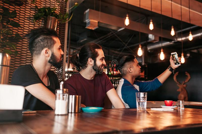 Group of arabian friends taking selfie in lounge bar. Mixed race young men having fun together stock image