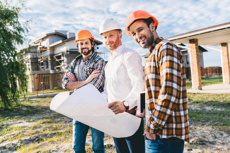 Group of architects with blueprint in garden. At construction site royalty free stock image
