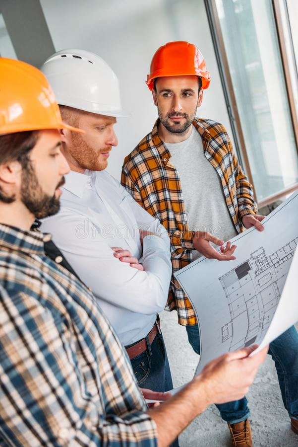 Group of architects with blueprint having conversation inside of. Constructing building royalty free stock images