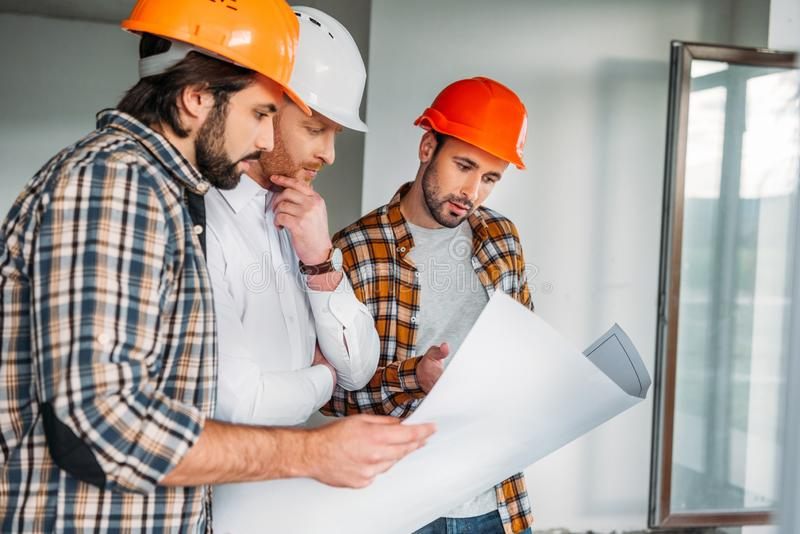 Group of architects with blueprint inside of. Constructing building royalty free stock photo