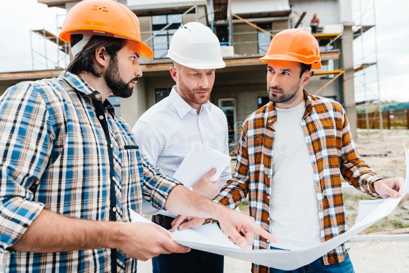 Group of architects with building plan having conversation in front of. Construction site royalty free stock photo