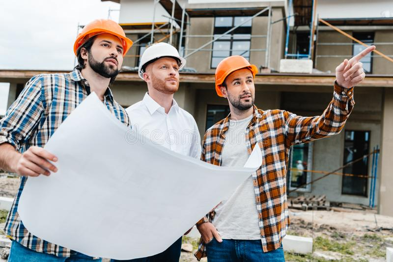 Group of architects with building plan standing in front of construction site. And looking away stock photos
