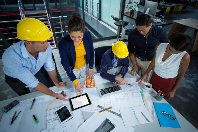 Group of architects discussing blueprint together. In office royalty free stock photo