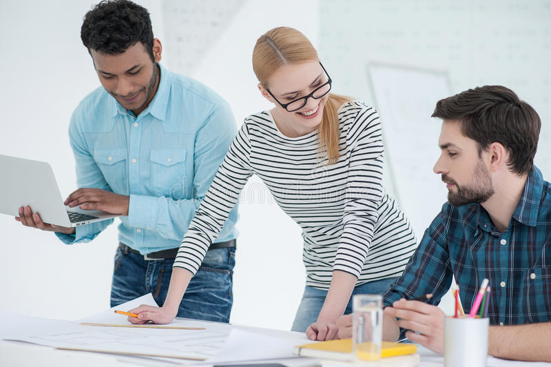 Group of architects discussing plans in modern office royalty free stock image