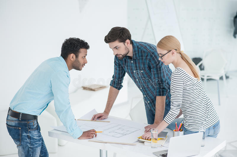 Group of architects discussing plans in modern office stock photos