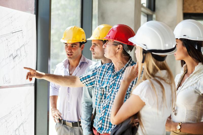 Senior construction manager and group of architects and experts discuss about construction project. stock photography