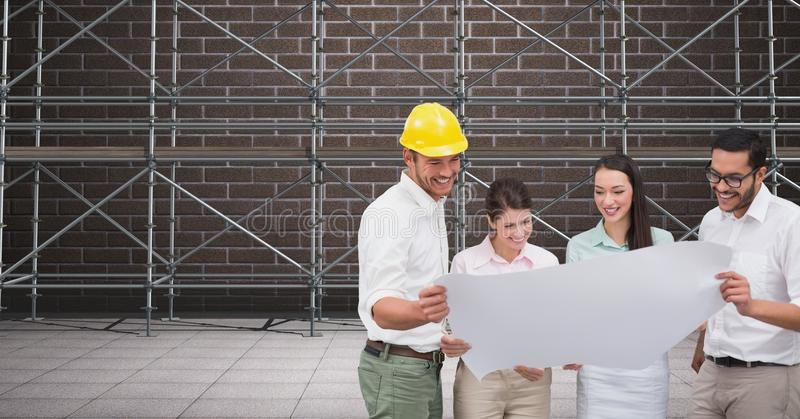 A group of architects looking a blueprint in front of 3D scaffolding stock images