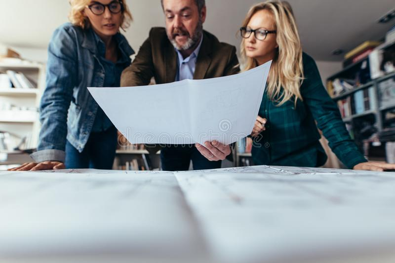 Group of architects over blueprints plans in office stock photo
