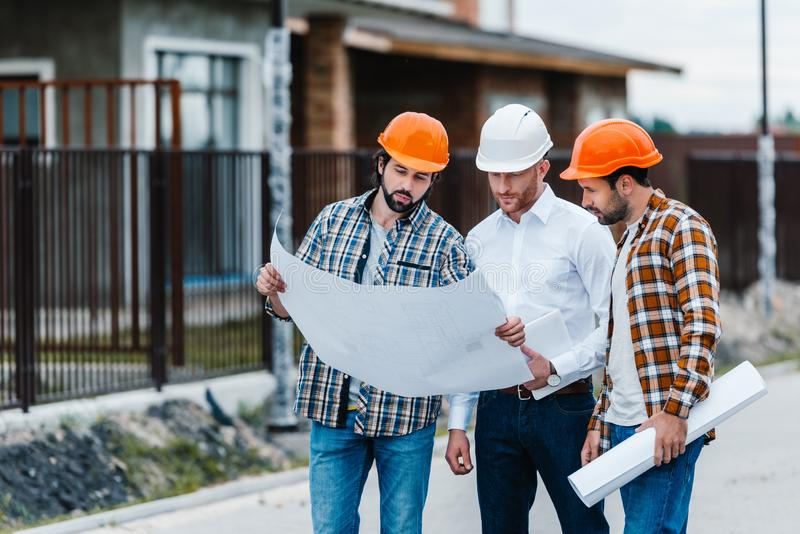 Group of architects standing on building street. With blueprints stock image