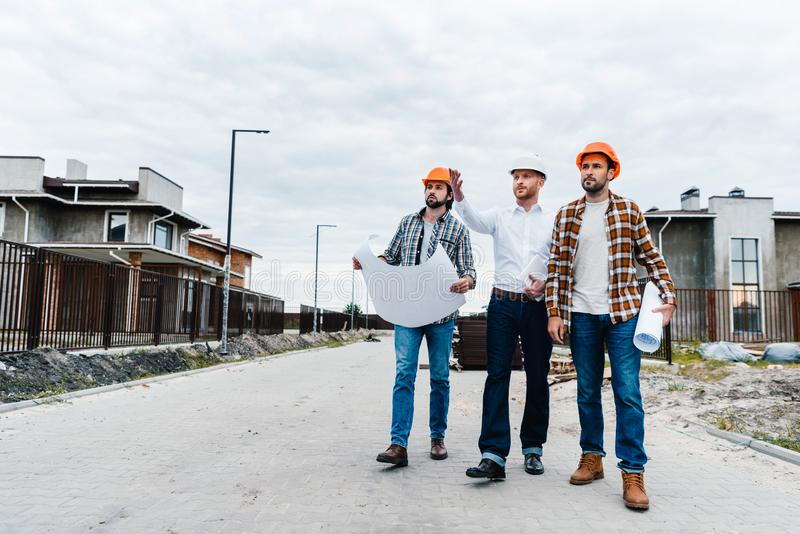Group of architects walking by constructing street. With blueprints royalty free stock photo