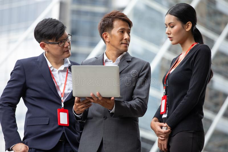 Group of asian Business people meeting With Digital laptop computer  discussing together with problem in work at city outdoors. royalty free stock photography
