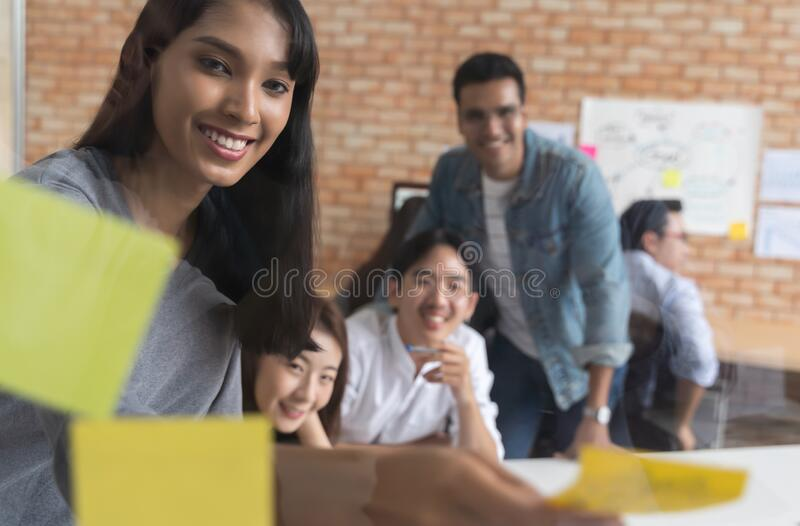 Group of Asian business people meeting at modern office .Young creative team use post it notes to share idea sticky note on glass royalty free stock image