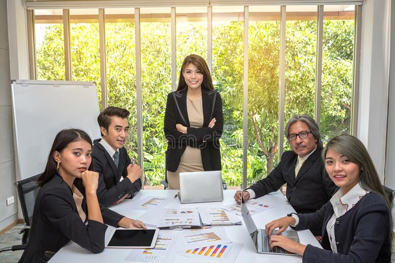 Group of asian business posing in meeting room. Working brainstorming at spacious board room at the office. Boss explaining plans royalty free stock image