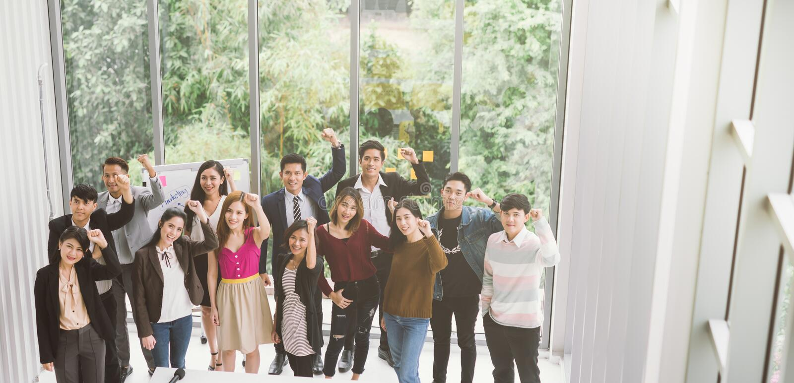 Group of asian business team raising arms success achievement Concept. royalty free stock image
