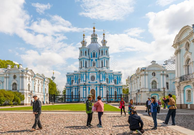 A group of Asian or Chinese tourists doing different pose in front of Blue-and-white Smolny Cathedral royalty free stock photography
