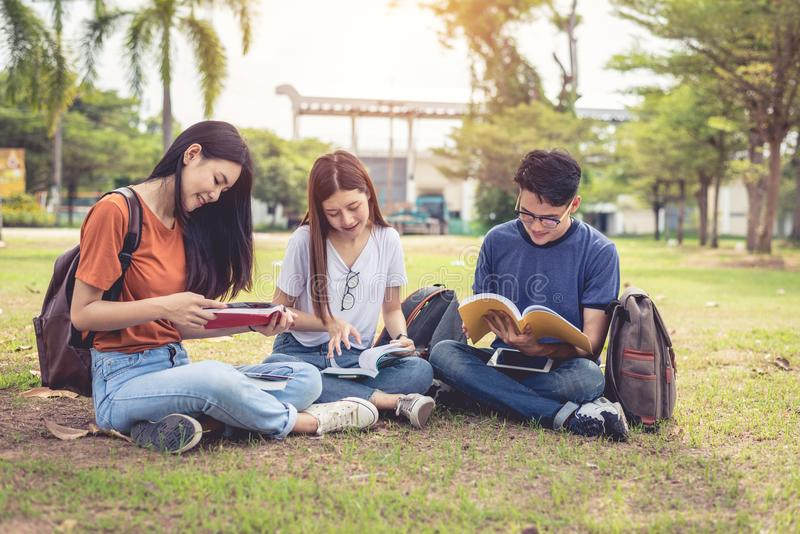 Group of Asian college student reading books and tutoring special class for exam on grass field at outdoors. Happiness and stock photo
