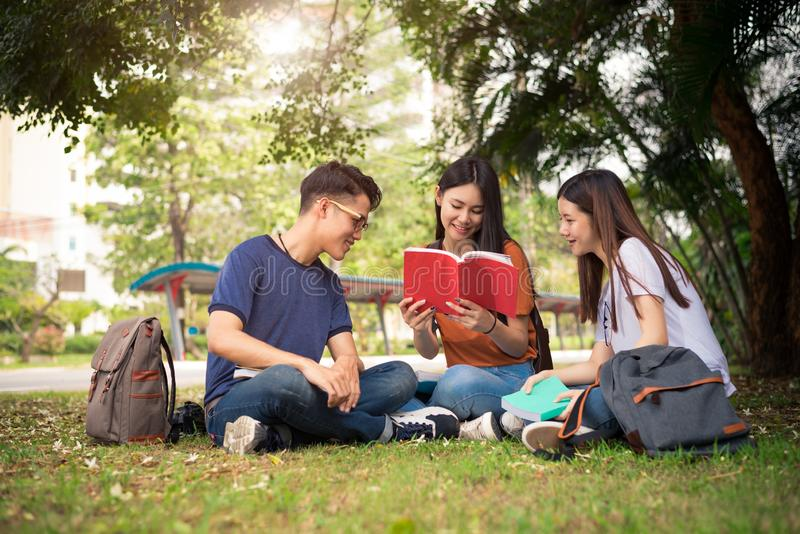 Group of Asian college student reading books and tutoring special class for exam on grass field at outdoors. Happiness and royalty free stock image