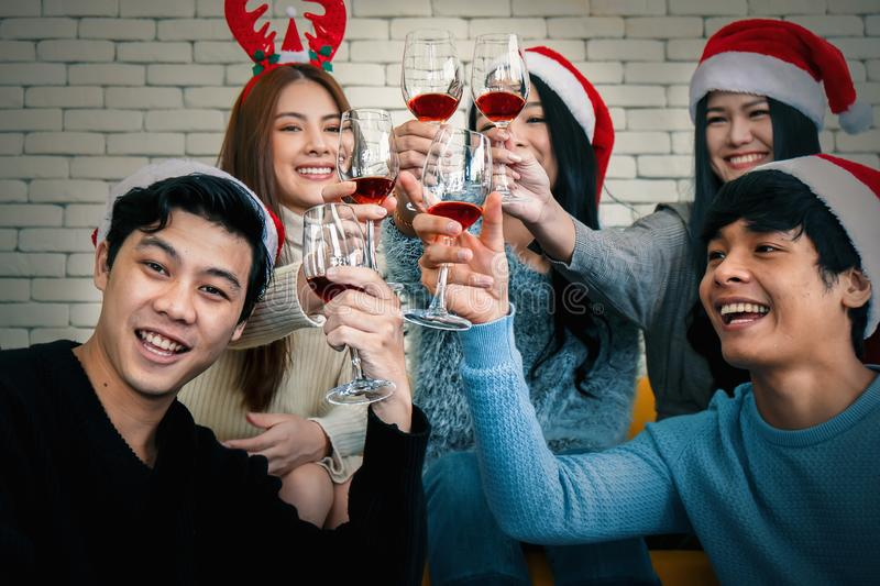 Group of asian friends having fun with christmas celebration party at home with wine stock photography