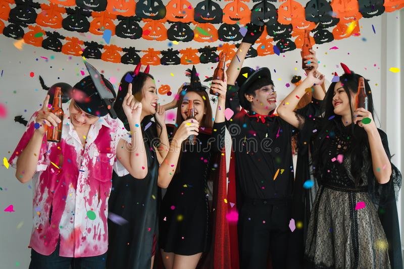 Group of asian friends in spooky costume having fun with dancing and drinking beer in halloween celebration party stock photos