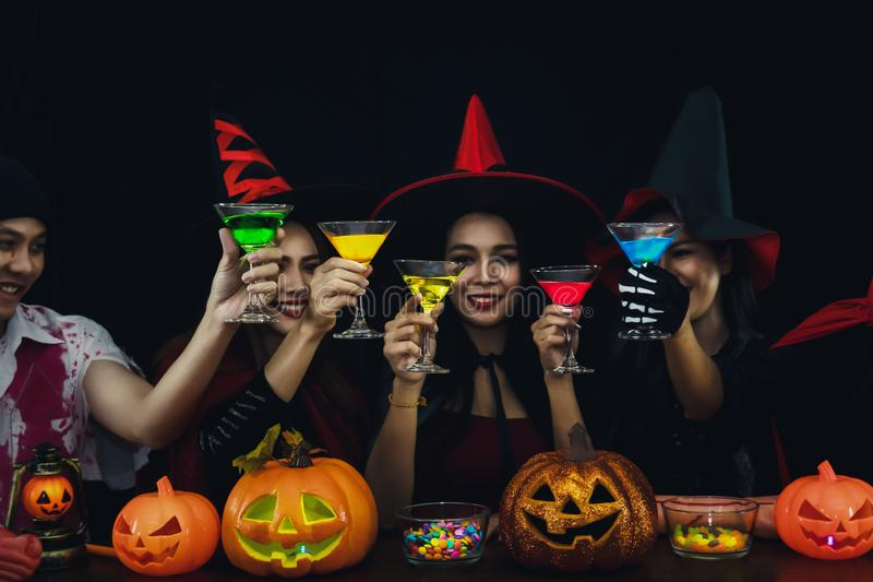 Group of asian friends in spooky costume having fun and drink cocktails at halloween celebration party in nightclub stock photography