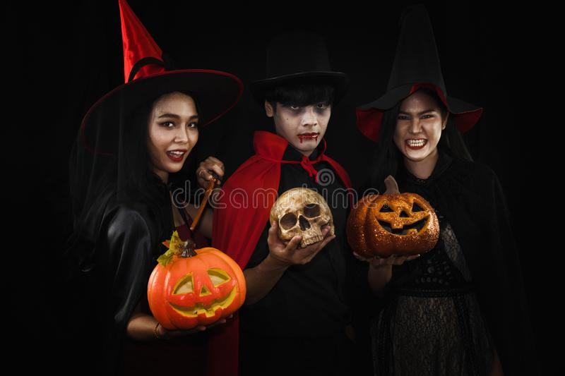 Group of asian friends in spooky costume of witch and vampire with pumpkin head and human skull posing at halloween celebration. Party in nightclub stock image