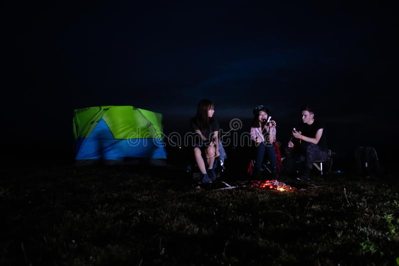 A group of Asian friends tourist drinking alcoholic beer and playing guitar together with happiness in Summer while having camping. And barbecue Marshmallows on stock photos