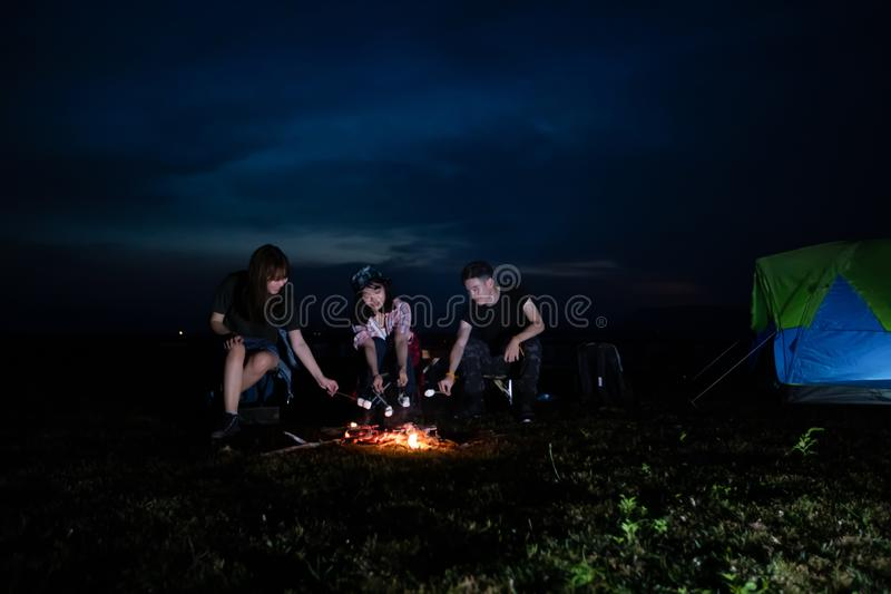 A group of Asian friends tourist drinking alcoholic beer and playing guitar together with happiness in Summer while having camping. And barbecue Marshmallows on royalty free stock image