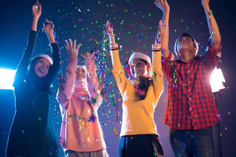 Group of Asian people celebrating New year party in night club with confetti. New year and Christmas party concept. Happiness and royalty free stock photo