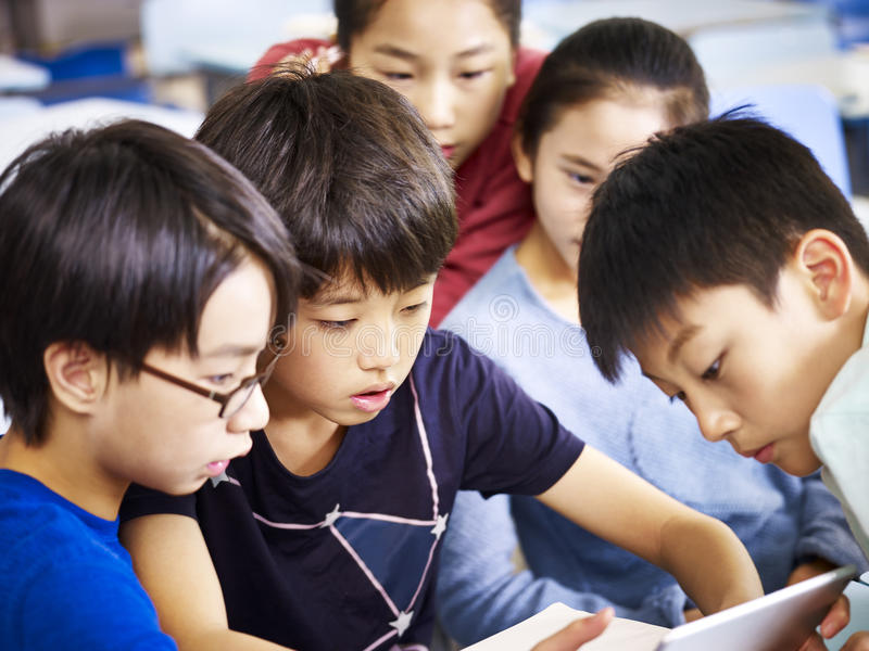 Group of asian pupil using tablet together royalty free stock photo