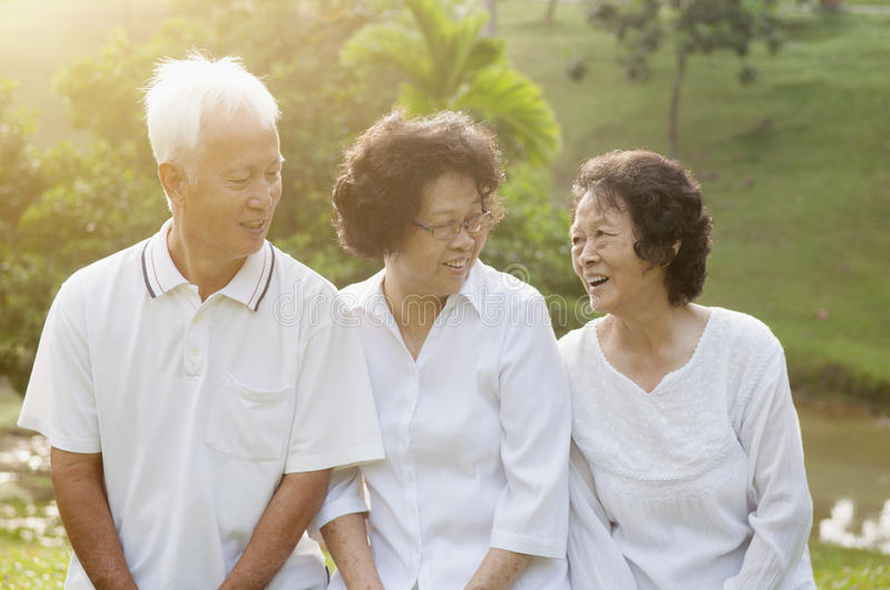 Group of Asian seniors at park. Group of healthy Asian seniors chatting at outdoor nature park, in morning beautiful sunlight at background stock photo