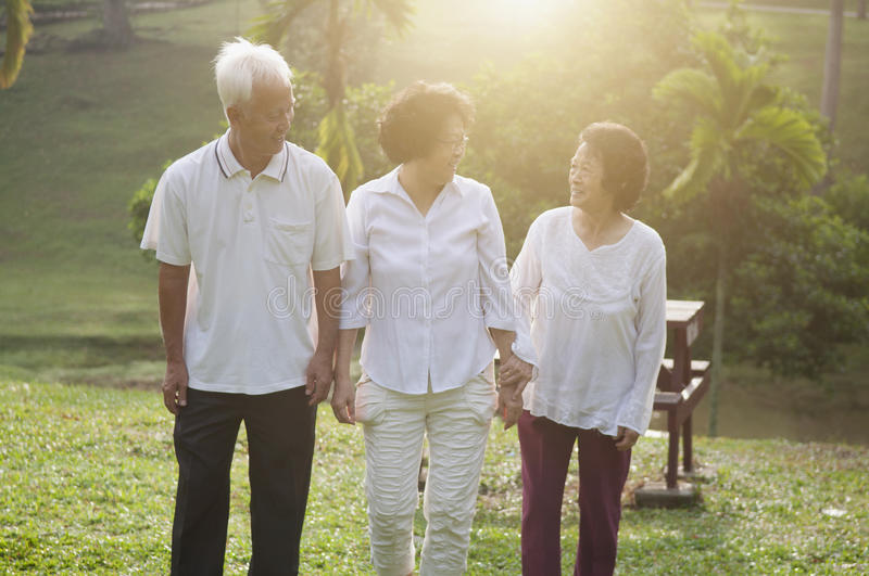 Group of Asian seniors walking at park. Group of healthy Asian seniors retiree walking at outdoor nature park, in morning beautiful sunlight at background royalty free stock images