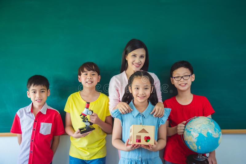 Shoolkids and teacher standing in front of blackboard royalty free stock image