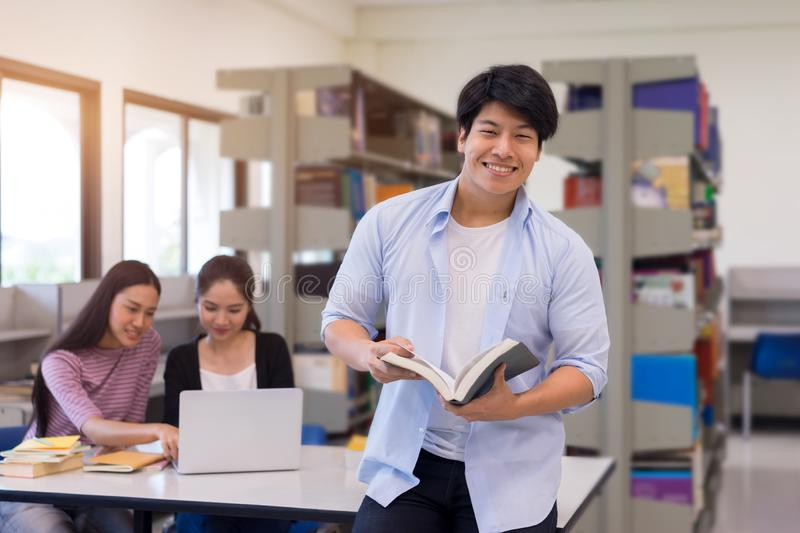 Group of Asian students studying together in library, learning a stock image