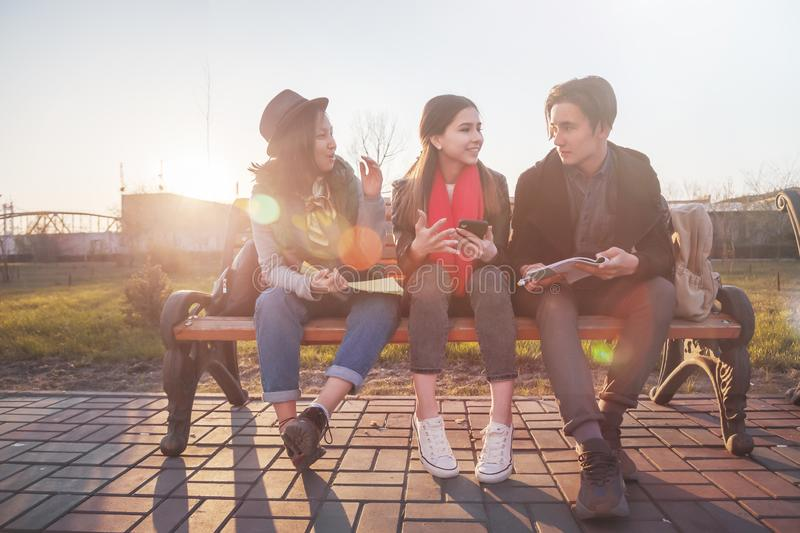 Group of Asian teenage students schoolchildren sitting on a bench in the park and preparing exams royalty free stock photography