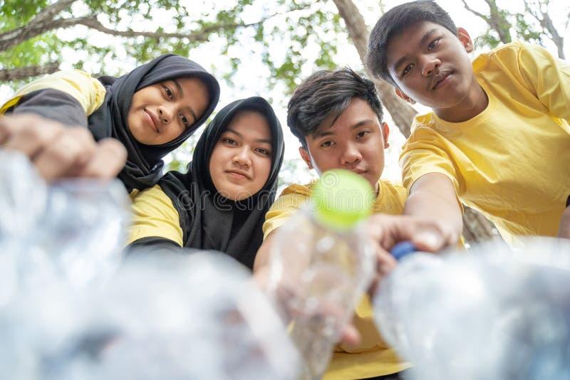 Group of asian teenage volunteers pick up bottle trash stock photography