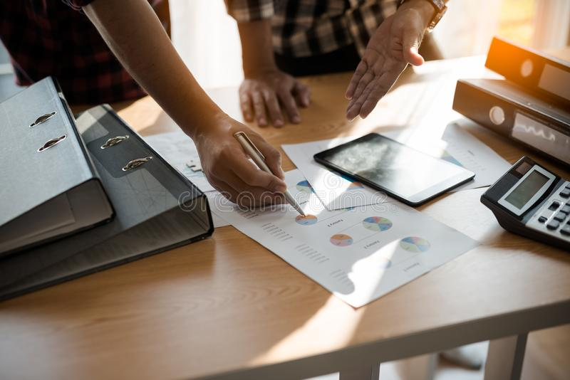 Group Asian Young Businessmen and woman discussing on stockmarket charts at office desk, they are business analyzing. stock image