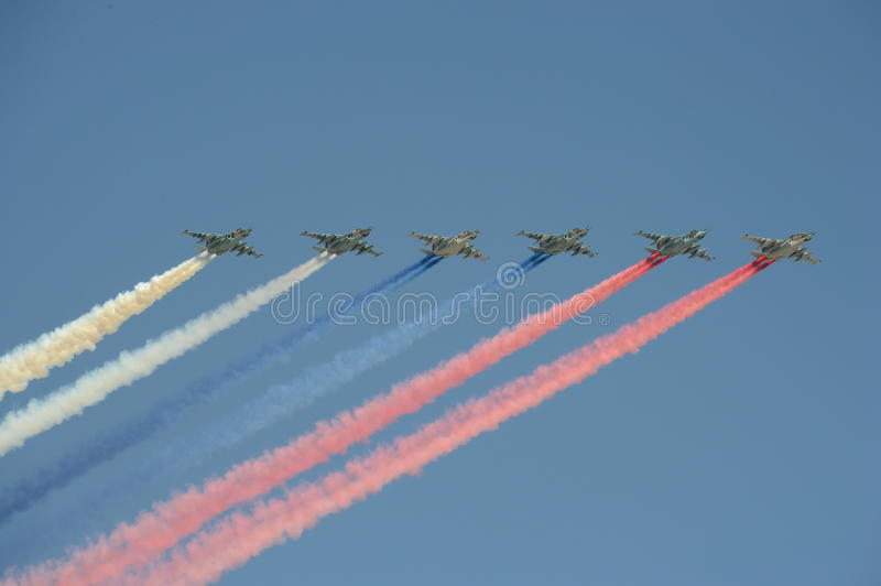 A group of assault plane Sukhoi Su-25 Grach NATO reporting name: `Frogfoot` in the sky smoke colors of Russian flag at the rehea royalty free stock photos