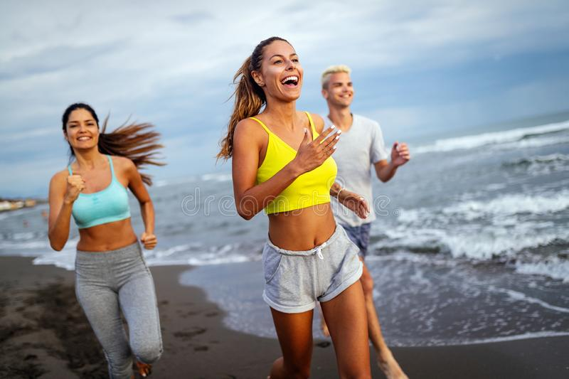 Group of athletes running on ocean front. Friends in sportswear training together outdoors. royalty free stock photos